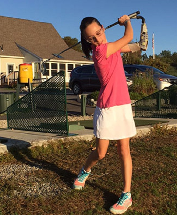 Christina, a young girl with a prosthetic arm dressed in a golf clothes, takes a swing on the green