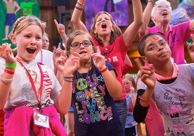 Kids laugh and play on stage at camp